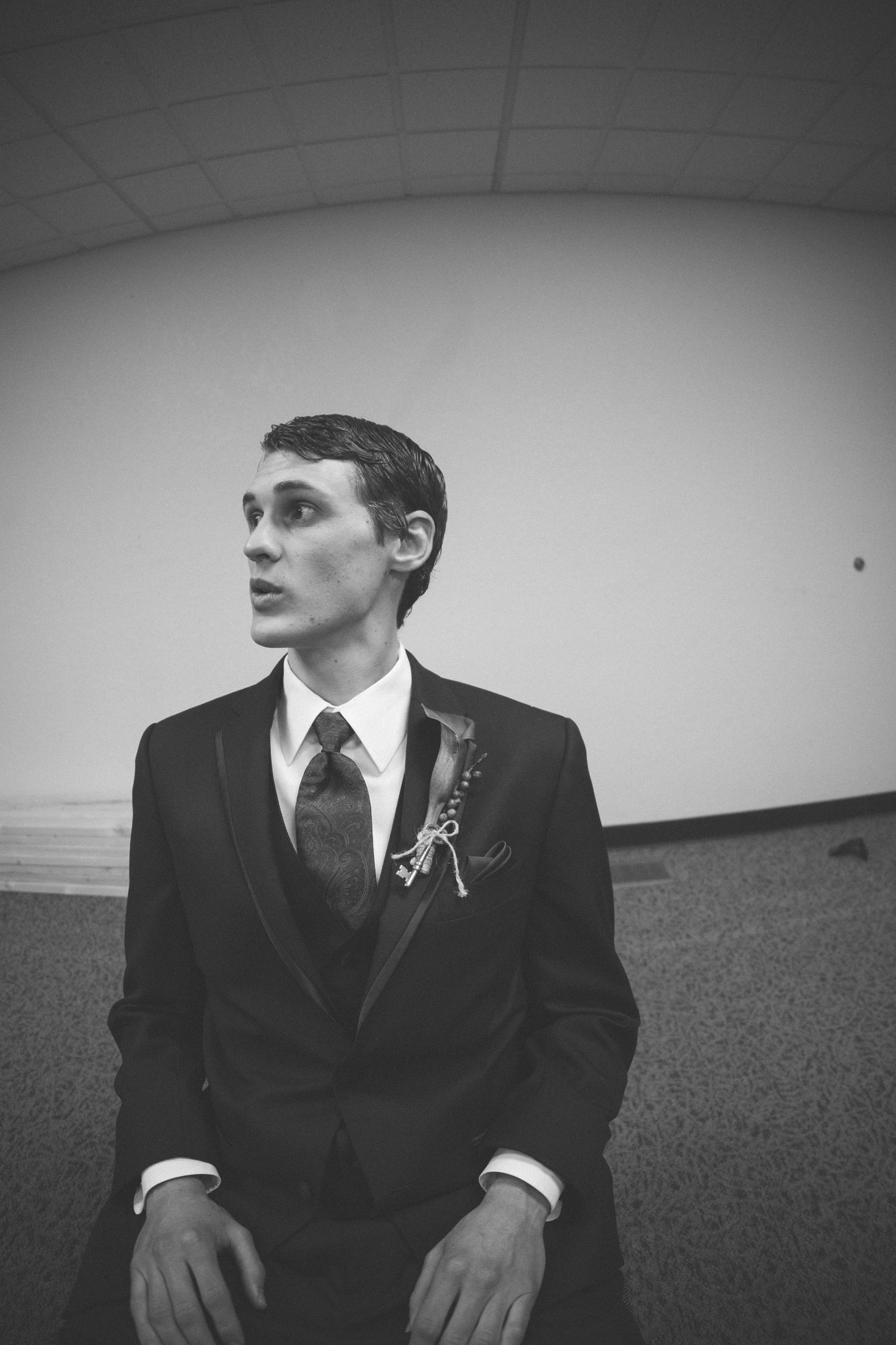 018-black-and-white-picture-of-groom-in-dressing-room-looking-surprised